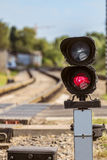 Routing traffic light with a red signal on railway. Railway crossing with forbidding traffic signal. Limited depth of field Royalty Free Stock Image