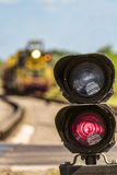 Routing traffic light with a red signal on railway. Railway semaphore signal prohibiting movement on a blurred background approaching train. Limited depth of Stock Images