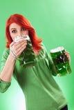 Roux appréciant la bière verte photo stock