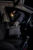 Rover de brekende vensters van een auto om zak te stelen royalty-vrije stock afbeelding