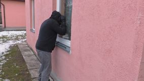 Robber with crowbar watching in window Stock Footage