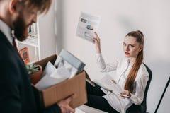 Rovesci l'uomo d'affari infornato con la scatola di cartone e la donna di affari arrabbiata in ufficio Immagine Stock Libera da Diritti
