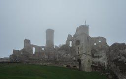 Rovina medievale del castello che si siede sopra la collina in nebbia pesante fotografia stock libera da diritti