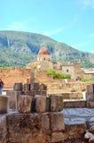 Rovine antiche nel Simat de la Valldigna Monastery sotto la luce solare e un cielo blu con una montagna alla parte posteriore Immagini Stock