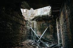 Rovine dell'interno del fabbricato industriale dopo il disastro o guerra o terremoto Soffitto crollato, mazzo di macerie e detrit Immagini Stock
