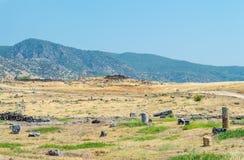 Rovine, resti nel campo nei precedenti delle colline della città antica di Hierapolis immagini stock