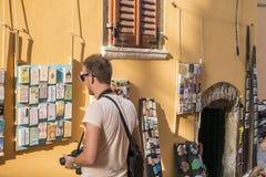Rovinj Kroatien - Juli 30, 2015: Turist som ser på souvenir Fotografering för Bildbyråer