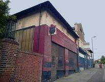 A row of abandoned stores with boarded up shop fronts with crumbling facades and peeling paint in an urban road. A row of abandoned stores with boarded up shop Royalty Free Stock Photos