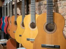 A row of acoustic guitars at music store stock images