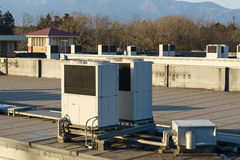 A row of air conditioning units on a rooftop. Royalty Free Stock Photos