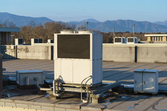 A row of air conditioning units on a rooftop. Royalty Free Stock Photography