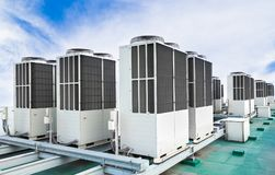 A row of air conditioning units on rooftop with blue sky. A row of air conditioning units on rooftop factory with blue sky Stock Photo