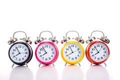Row of Alarm Clocks. A row of vintage looking brightly colored alarm clocks on a white background with copy space stock photography
