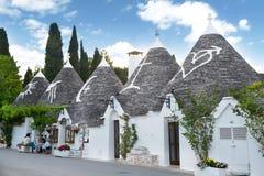 A row of amazing white houses trulli in Albrerobello, Puglia, It. Alberobello, Italy - 11 May, 2014:  a fine white housed street in Alberobello, Italy, with Royalty Free Stock Images