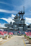 Row of American flags at Pearl Harbor memorial. This is the USS Missouri with a blue sky on the background Stock Images