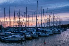 Row of anchored sailing boats in purple evening sunlight. Row of anchored sailing boats at a small boat harbor at the Swedish east coast,  with masts and lines Royalty Free Stock Image