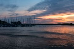 Small boat harbor with sailing boats in pink evening sunlight. Row of anchored sailing boats at a small boat harbor at the Swedish east coast,  with masts and Royalty Free Stock Photo
