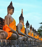 A row of ancient buddha statues in front of ruin pagoda Royalty Free Stock Photography
