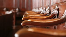 A row of ancient chairs. Shallow depth of field. Handles of ancient chairs in an old interior with natural light stock video footage