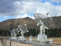 Row of antennas at the Dominion Radio Astrophysical Observatory at White Lake near Penticton BC. A row of antennas with hills, clouds and blue sky in background stock photo
