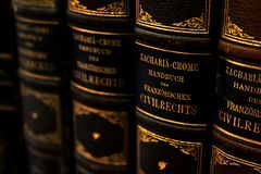 Row of antique handbooks about the French civil law with leather covers and German titles in golden letters royalty free stock photography