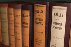 Row of antique books with leather covers and German titles in black letters. The literature is about historical sources related to Swiss history royalty free stock photo