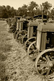 Row of Antique Tractors Sepia. A row of antique tractors from the 1920's and 1930's.  Sepia tone to resemble an old time photgraph Royalty Free Stock Images