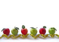 Row of Apples with curly tape measure Royalty Free Stock Image