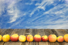 Row of apples on wood. Row of apples on weathered wood with wispy cloud background Royalty Free Stock Image