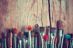 Row of artist paintbrushes closeup on old wooden table, retro st. Row of artist paintbrushes closeup on old wooden rustic table, retro stylized Royalty Free Stock Photos