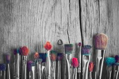 Row of artist paintbrushes with colorful bristle, retro black and white stylized. Stock Photos