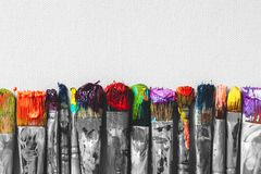 Row of artist paintbrushes with colorful bristle closeup. On artistic canvas background, retro black and white stylized royalty free stock photo
