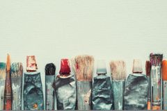 Row of artist paintbrushes and paint tubes closeup on artistic canvas. Row of artist paintbrushes and paint tubes closeup on artistic canvas background, retro stock photo