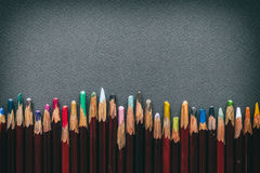 Row of artist pastel pencils on gray pastel paper sheet. Royalty Free Stock Photo