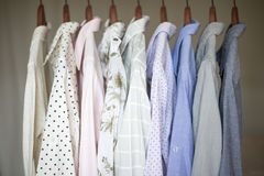 A row of assorted business shirts for women on hangers in a closet Royalty Free Stock Photo
