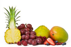 Row of Assorted Fruit. Half of a pineapple, raspberries, red grapes, strawberries, blueberries and mangoes, isolated Stock Photos