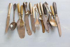 Row of assorted vintage cutlery. Row of assorted tarnished vintage cutlery with knives, forks and spoons, some with old bone handles viewed from above on a royalty free stock photo