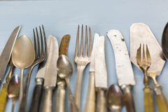 Row of assorted vintage cutlery. Row of assorted tarnished vintage cutlery with knives, forks and spoons, some with old bone handles viewed from above on a stock photos