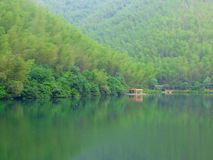 A row awnings in the middle of lake and mountains. A row orange awnings for tourists to rest near a lake with mountains background in south hill bamboo sea royalty free stock photo