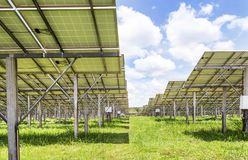Row of back side view photovoltaics solar panels in solar power station royalty free stock photo