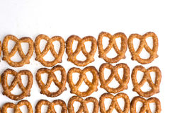 A row of baked pretzels on white. A row of baked pretzels on white stock photography