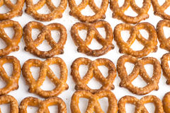 A row of baked pretzels on white. A  row of baked pretzels on white royalty free stock image