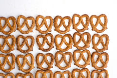Row of baked pretzels on white. Row of baked pretzels on white stock photography
