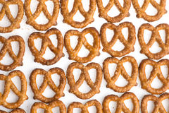 A row of baked pretzels on white. A close up row of baked pretzels on white royalty free stock photos