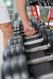 Row of barbells. Vertical image of a male athlete taking a dumbbell from a row Royalty Free Stock Photography