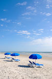 Row of Beach Chairs with Blue Umbrella Royalty Free Stock Photography