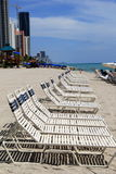 Row of beach chairs on hot sandy shoreline Royalty Free Stock Image