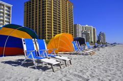 Row of beach chairs. A row of beach chairs lines the beach in front of condos and hotels Royalty Free Stock Photo