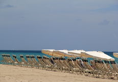 Row of beach chairs and shade umbrellas. Inviting row of beach chairs and big shade umbrellas on the edge of the ocean,begs vacationers to come and enjoy the Royalty Free Stock Image