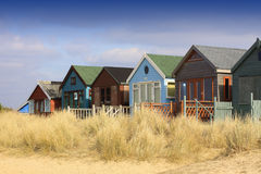 Row of Beach Huts. A landscape format image of a row of wooden beach huts with sand dunes and grasses to front. Located in Christchurch, Dorset Hampshire UK Stock Image